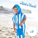child wearing a poncho at the beach