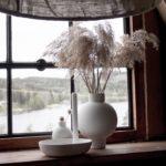white vase beside a window